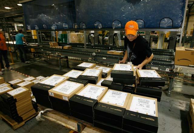 Сотрудник на складе Amazon готовит к отправке планшеты Kindle